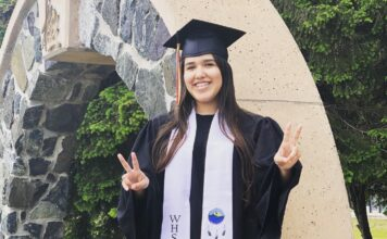 Girl in graduation clothing doing a piece sign